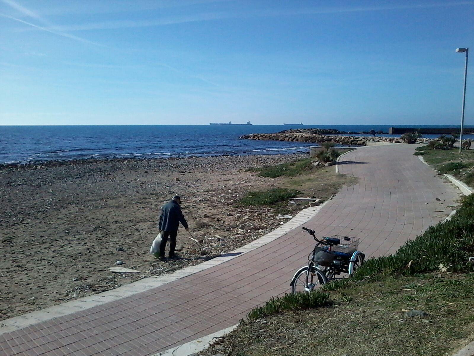 Il signore che raccoglie la sporcizia nella spiaggia della Marina di Civitavecchia simbolo dell'insuccesso politico